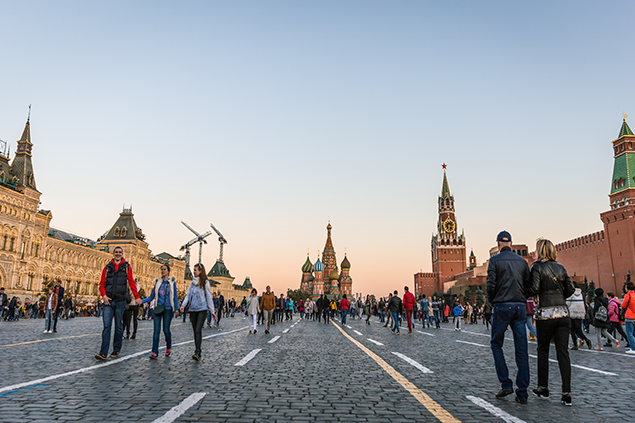Tourists walk around historical Red Square surrounded by Gum, Saint Basil's Cathedral and Kremlin Palace.