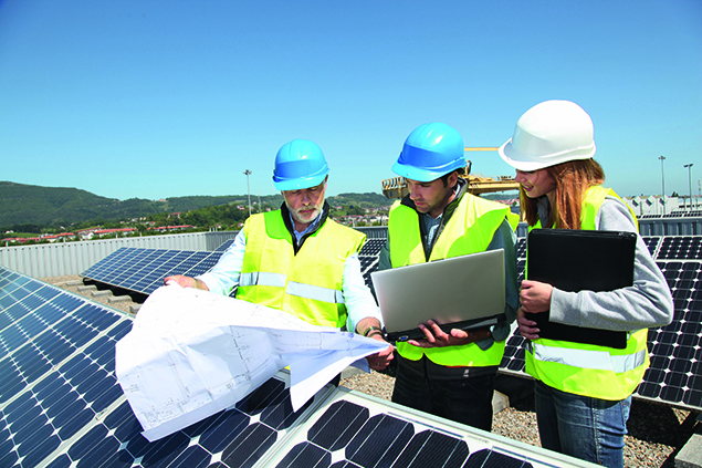 Engineers with plans near photovoltaic panels